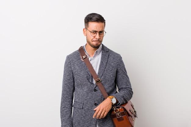 Giovane uomo filippino d'affari contro un muro bianco confuso, si sente dubbioso e incerto. Foto Premium