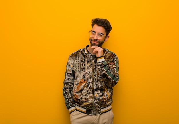 Giovane uomo freddo che dubita e confuso Foto Premium
