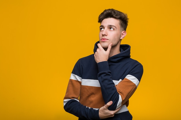 Giovane uomo freddo che indossa una felpa con cappuccio guardando lateralmente con espressione dubbiosa e scettica. Foto Premium