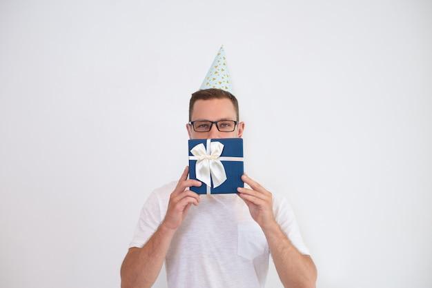 Giovane uomo in cappello di partito che copre la bocca con confezione regalo Foto Gratuite