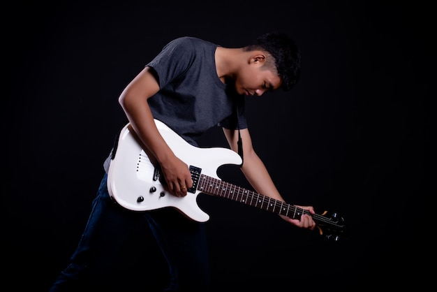 Giovane uomo in maglietta scura con chitarra elettrica Foto Gratuite