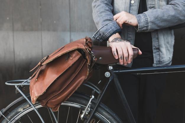 Giovane uomo in piedi con la borsa marrone in bicicletta Foto Gratuite