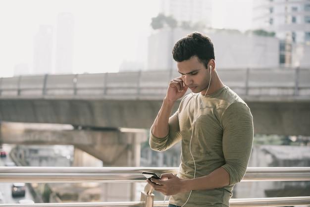 Giovane uomo indiano bello indossare auricolari ascoltando musica Foto Premium