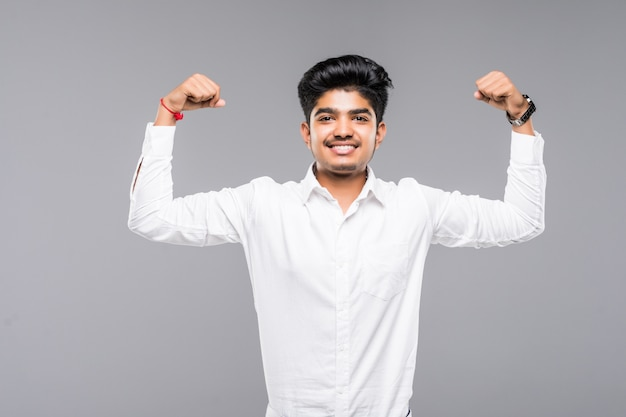 Giovane uomo indiano felice che mostra il bicipite sopra la parete grigia Foto Gratuite
