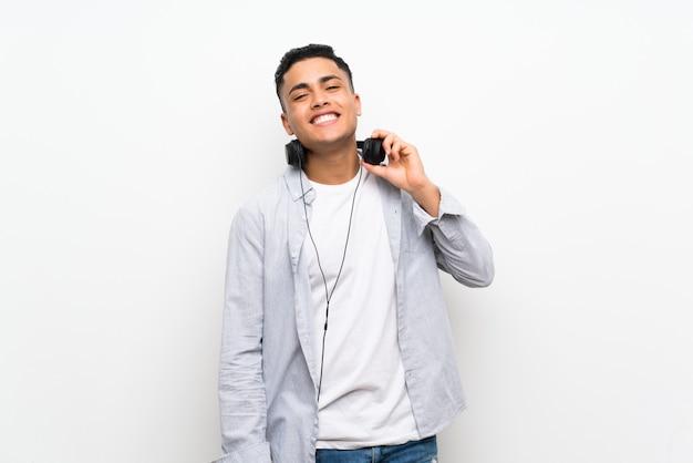 Giovane uomo isolato muro bianco con auricolari Foto Premium