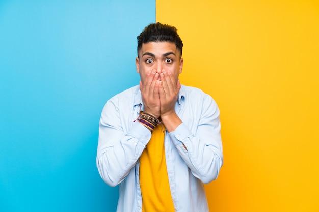 Giovane uomo isolato su sfondo colorato con sorpresa espressione facciale Foto Premium