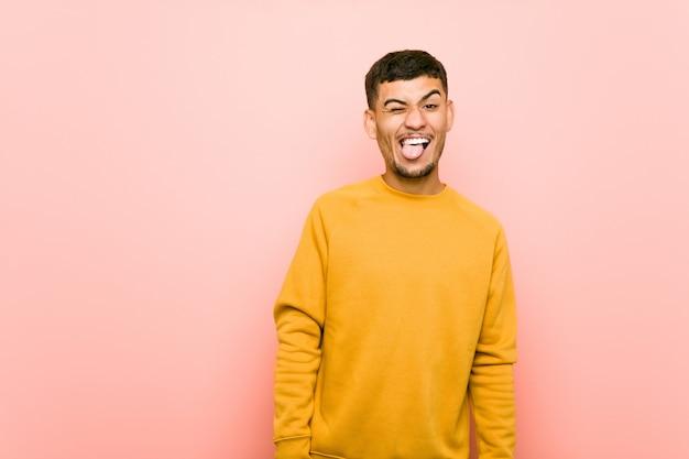 Giovane uomo ispanico divertente e amichevole che attacca fuori lingua. Foto Premium