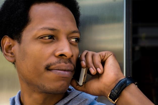 Giovane uomo latino che parla sul telefono cellulare fuori. Foto Premium