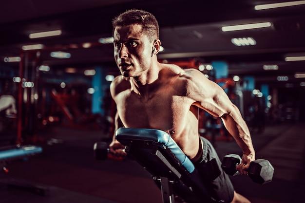 Giovane uomo muscolare che fa esercizio duro con le teste di legno per i delta posteriori delle spalle sul banco di addestramento alla palestra Foto Premium