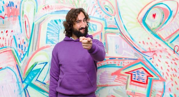 Giovane uomo pazzo barbuto che punta alla fotocamera con un sorriso soddisfatto, fiducioso, amichevole, scegliendovi sulla parete dei graffiti Foto Premium