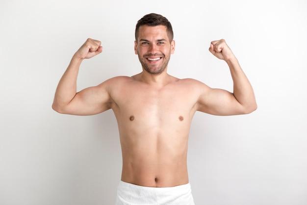 Giovane uomo senza camicia che flette i suoi muscoli contro la parete bianca Foto Gratuite