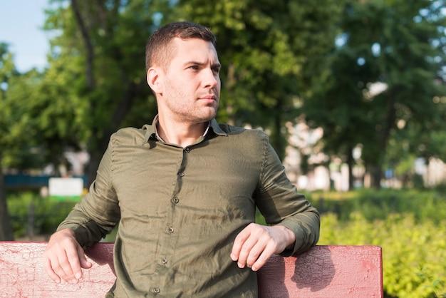 Giovane uomo serio seduto sulla panchina nel parco Foto Gratuite