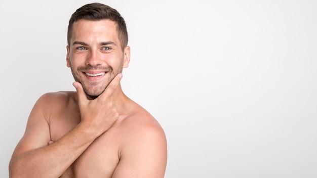 Giovane uomo sorridente bello che esamina macchina fotografica e che tiene mano sul mento mentre stando contro la parete bianca Foto Gratuite