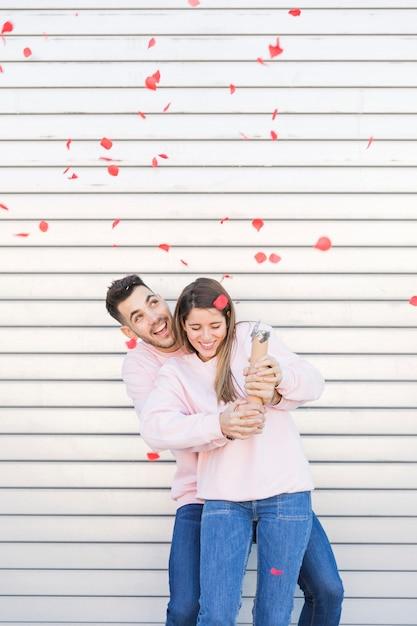 Giovane uomo sorridente che abbraccia donna felice attraente con esplodere popper partito Foto Gratuite