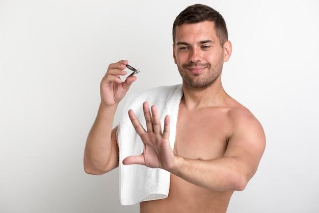 Giovane uomo sorridente che guarda la sua mano dopo il taglio delle unghie Foto Gratuite