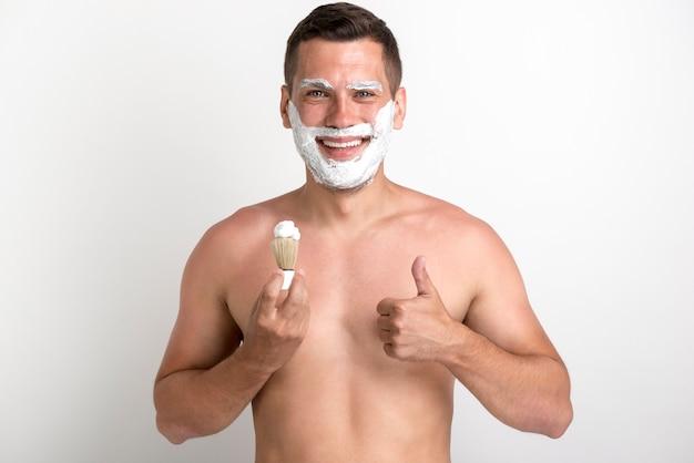 Giovane uomo sorridente che mostra pollice sul gesto mentre radendosi Foto Gratuite