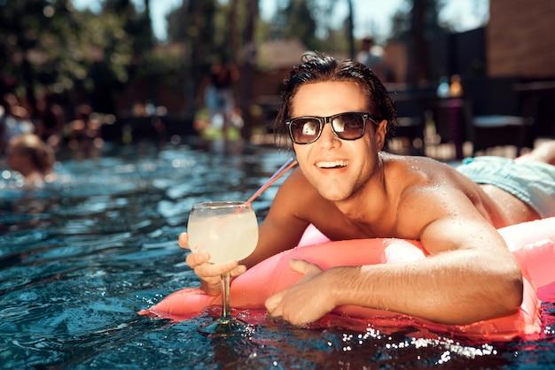 Giovane uomo sorridente in occhiali da sole sul materasso ad aria Foto Premium