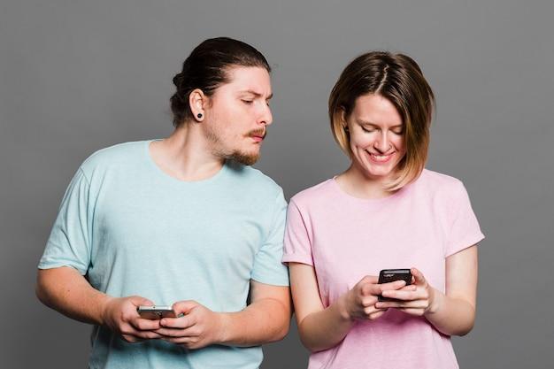 Giovane uomo spiare e sbirciare allo smartphone della sua ragazza utilizzando il telefono cellulare Foto Gratuite