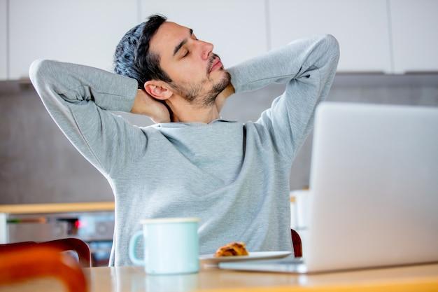 Giovane uomo stanco che si siede al tavolo con computer claptop Foto Premium