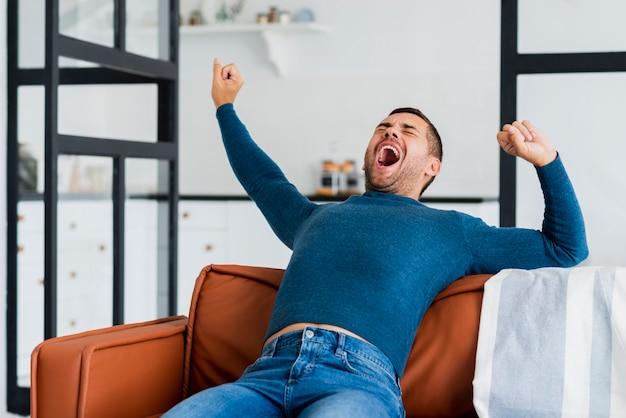 Giovane uomo sul divano sbadigliando Foto Gratuite