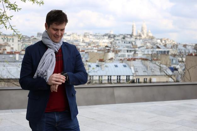 Giovane uomo sul tetto a parigi guarda l'orologio da polso vicino alla basilica del sacro cuore Foto Premium