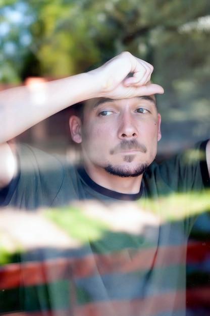 Giovane uomo triste con i baffi dietro il vetro in depressione Foto Premium