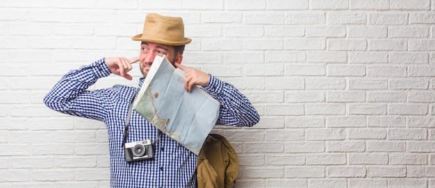 Giovane uomo viaggiatore che indossa zaino e una macchina fotografica d'epoca che copre le orecchie con le mani, arrabbiato e stanco di sentire un po 'di suono. in possesso di una mappa. Foto Premium