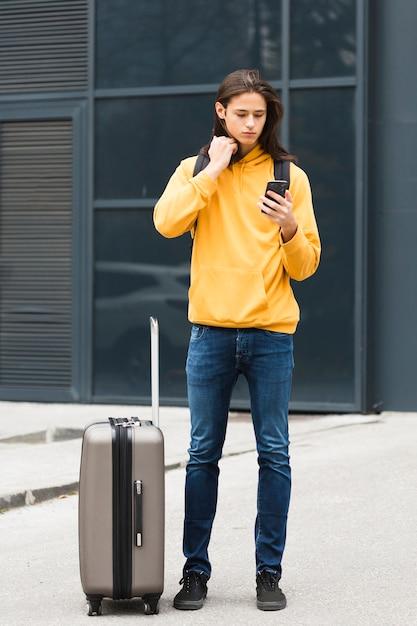 Giovane viaggiatore bello che controlla il suo telefono Foto Gratuite