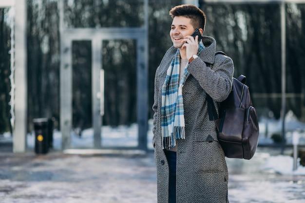 Giovane viaggiatore bello dell'uomo che per mezzo del telefono fuori Foto Gratuite