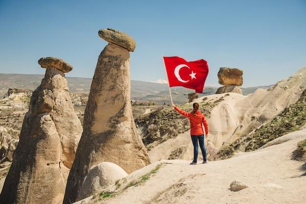 Giovane viaggiatore con bandiera turca nel paesaggio desertico della cappadocia Foto Premium