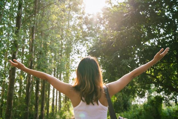 Giovane viaggiatore felice della donna asiatica con lo zaino che cammina nella foresta. Foto Gratuite