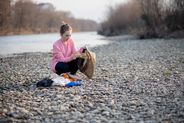 Giovane volontaria femminile che raccoglie immondizia sul fiume Foto Premium