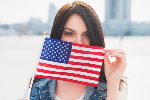 Giovane volto femminile di copertura con bandiera americana Foto Gratuite