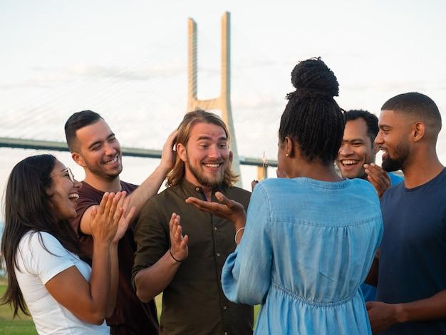 Giovani allegri che fanno sorpresa per l'amico maschio. donna afroamericana che presenta il muffin al cioccolato con la stella filante. concetto di sorpresa Foto Gratuite