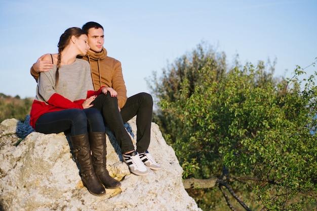 Giovani amanti al tramonto in montagna Foto Premium