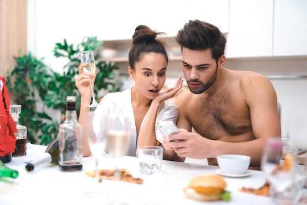 Giovani amanti che guardano le foto dopo una pazza festa di sesso Foto Premium
