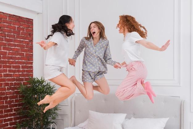 Giovani amiche che saltano nel letto Foto Gratuite