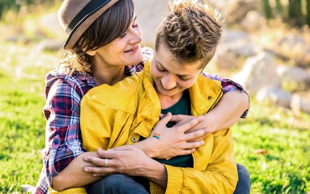 Giovani amiche innamorate che condividono il tempo insieme al viaggio di viaggio che abbraccia al parco Foto Premium