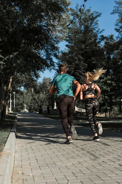 Giovani amici che corrono nel parco Foto Gratuite