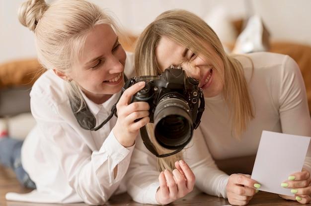 Giovani amici che utilizzano una macchina fotografica professionale Foto Gratuite