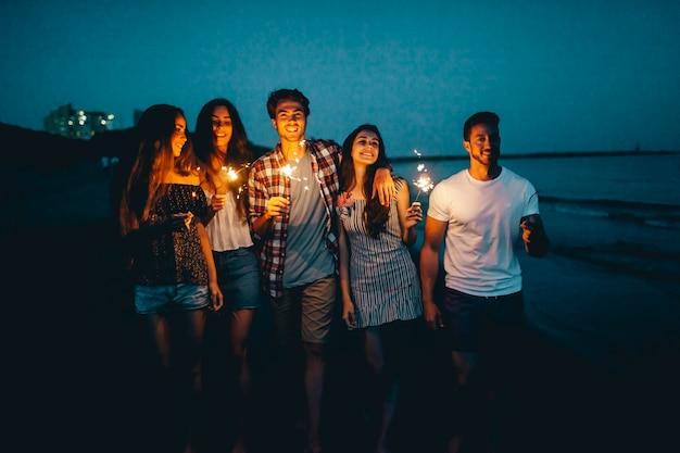 Giovani amici con sparklers in una spiaggia notturna Foto Gratuite