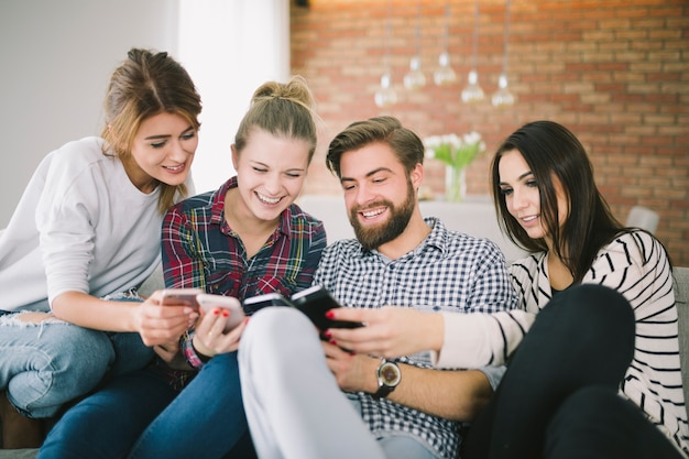 Giovani amici eccitati con gli smartphone che si divertono ...