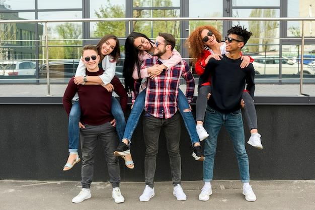 Giovani amici maschi che trasportano sulle spalle le loro amiche Foto Gratuite
