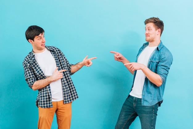 Giovani amici maschi facendo facce buffe che indicano le dita gli uni agli altri su sfondo blu Foto Gratuite