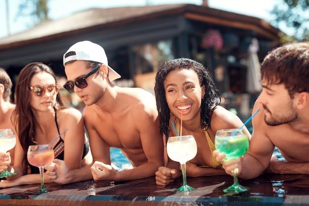 Giovani amici sorridenti con cocktail a bordo piscina Foto Premium