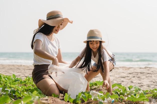 Giovani attivisti felici asiatici della famiglia che raccolgono rifiuti di plastica sulla spiaggia. i volontari asiatici aiutano a mantenere la natura pulita e a raccogliere i rifiuti. concetto sui problemi di inquinamento ambientale. Foto Gratuite