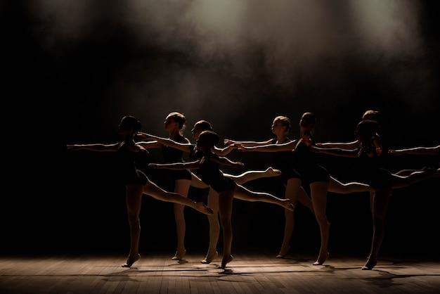 Giovani ballerine che provano nella classe di balletto. eseguono diversi esercizi coreografici e si trovano in posizioni diverse. Foto Premium