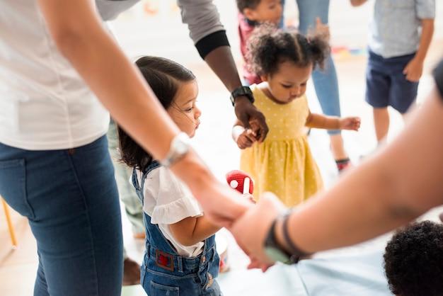 Giovani bambini diversi in piedi con i loro genitori Foto Premium