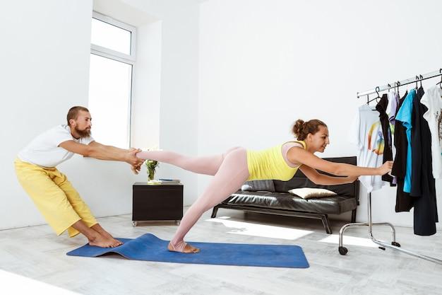 Giovani belle asana allegre di yoga del partner di addestramento delle coppie a casa. Foto Gratuite