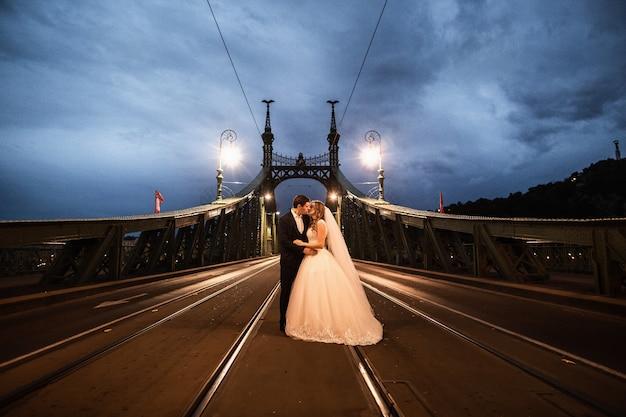 Giovani belle coppie alla moda delle persone appena sposate su un ponte a budapest Foto Premium